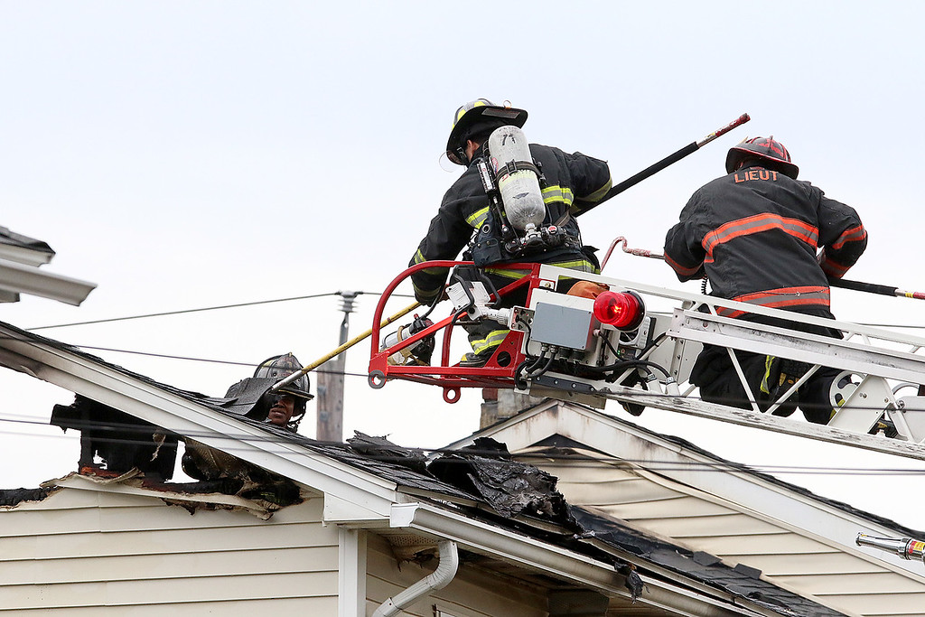 . Fire fighters check out the roof of the home at 8 Eden Glen Street after it was secured by police after a standoff and blaze in Leominster on Monday, Oct. 16, 2017. SENTINEL & ENTERPRISE / JOHN LOVE