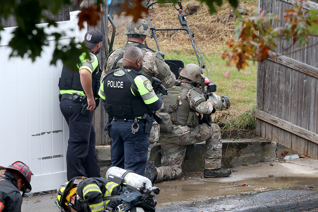 . A State police unit gets ready to enter during a standoff and blaze at 8 Eden Glen Street in Leominster on Monday, Oct. 16, 2017. SENTINEL & ENTERPRISE / JOHN LOVE