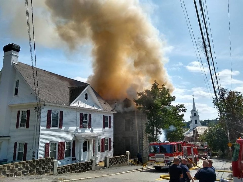 . Fitchburg firefighters work to slow a fast-moving fire that heavily damaged a Prospect Street home in Fitchburg on Sunday. PHOTO COURTESY OF PHIL SWEENEY