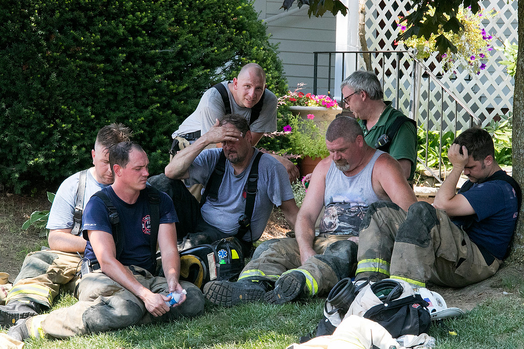 . A fire broke out at 50 Main Street in Pepperell at round 8:30 am arcoss the street from Dunkin Donuts on Tuesday, July 30, 2019. Fire relax in the shade after fighting the fire in 90+ heat. SENTINEL & ENTERPRISE/JOHN LOVE