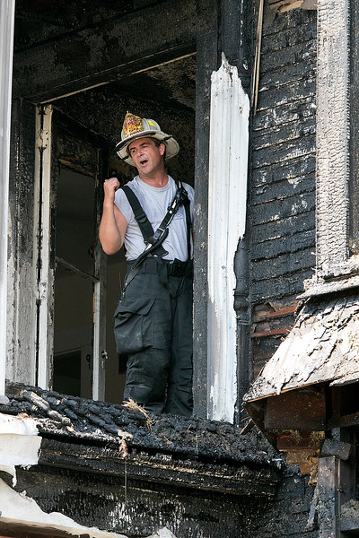 A fire broke out at 50 Main Street in Pepperell at round 8:30 am arcoss the street from Dunkin Donuts on Tuesday, July 30, 2019. Deputy Chief John Rose yells down to other firefighters from a door to a porch on the second floor after the fire was out. SENTINEL & ENTERPRISE/JOHN LOVE