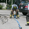 A fire broke out at 50 Main Street in Pepperell at round 8:30 am arcoss the street from Dunkin Donuts on Tuesday, July 30, 2019. A Pepperell Firefighter rolls up one of their hoses after they put out the fire. SENTINEL & ENTERPRISE/JOHN LOVE