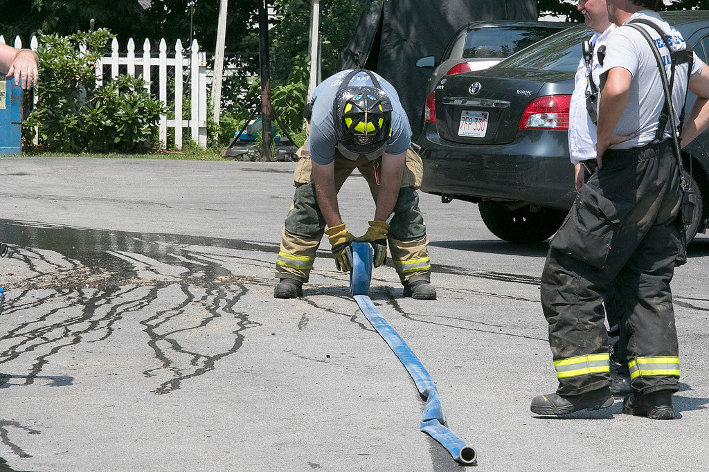 . A fire broke out at 50 Main Street in Pepperell at round 8:30 am arcoss the street from Dunkin Donuts on Tuesday, July 30, 2019. A Pepperell Firefighter rolls up one of their hoses after they put out the fire. SENTINEL & ENTERPRISE/JOHN LOVE