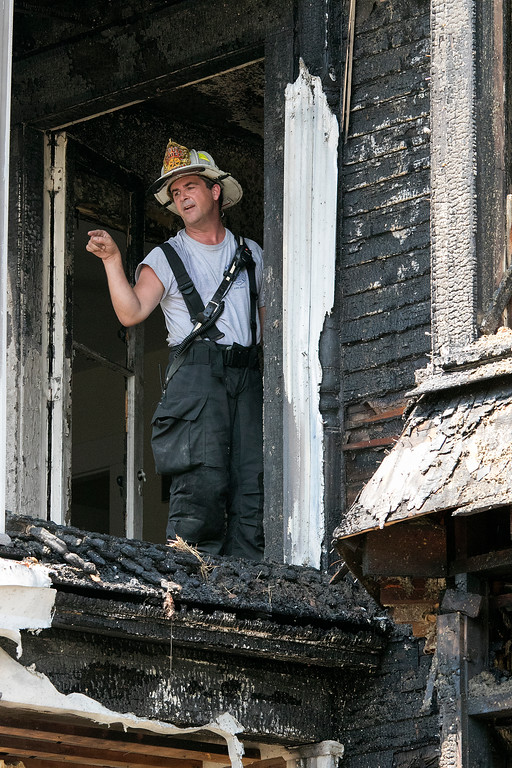 . A fire broke out at 50 Main Street in Pepperell at round 8:30 am arcoss the street from Dunkin Donuts on Tuesday, July 30, 2019. Deputy Chief John Rose yells down to other firefighters from a door to a porch on the second floor after the fire was out. SENTINEL & ENTERPRISE/JOHN LOVE