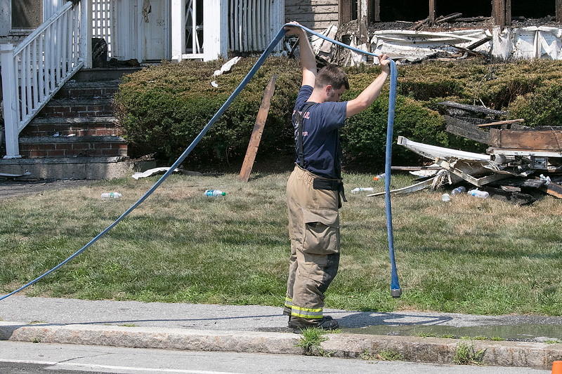 A fire broke out at 50 Main Street in Pepperell at round 8:30 am arcoss the street from Dunkin Donuts on Tuesday, July 30, 2019. A Pepperell Firefighter gets ready to roll up one of their hoses after they put out the fire. SENTINEL & ENTERPRISE/JOHN LOVE