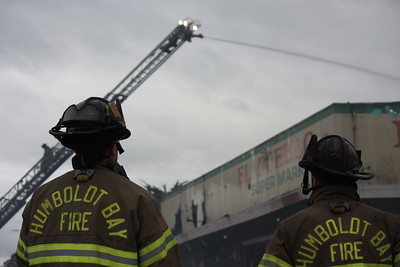 Humboldt Bay Fire firefighters watch as a ladder hose sprays water on to the El Pueblo Market in Eureka on Wednesday morning. (Will Houston - The Times-Standard)