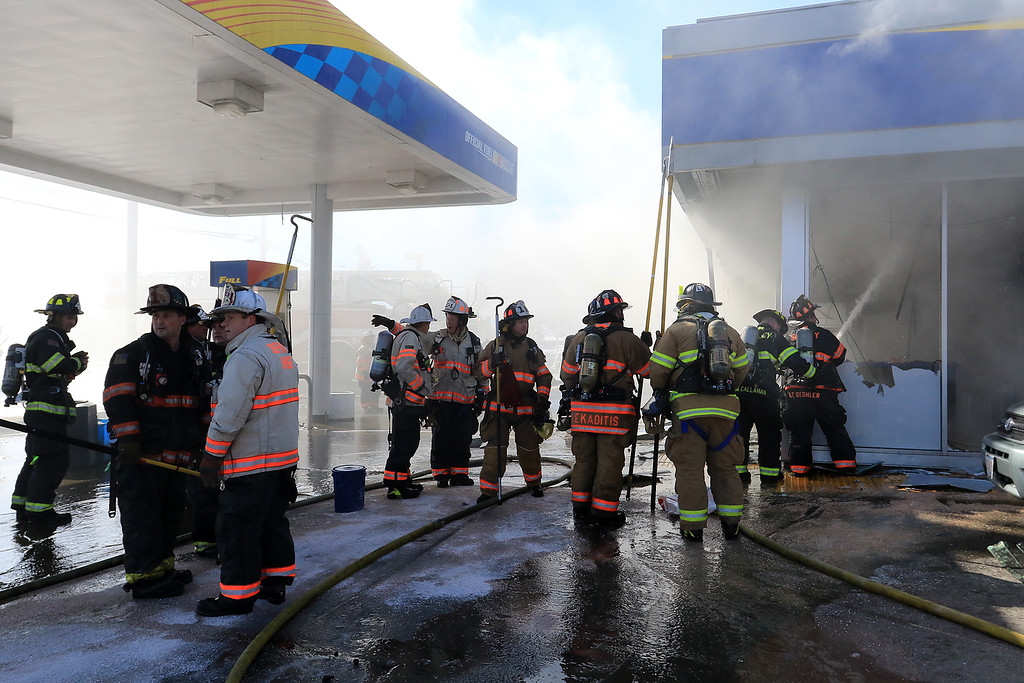. A fire broke out at the Sunoco station on Route 13 in Leominster early on Thursday morning. Firefighters spray down the waiting room at the station as they fight the fire. SENTINEL & ENTERPRISE/JOHN LOVE