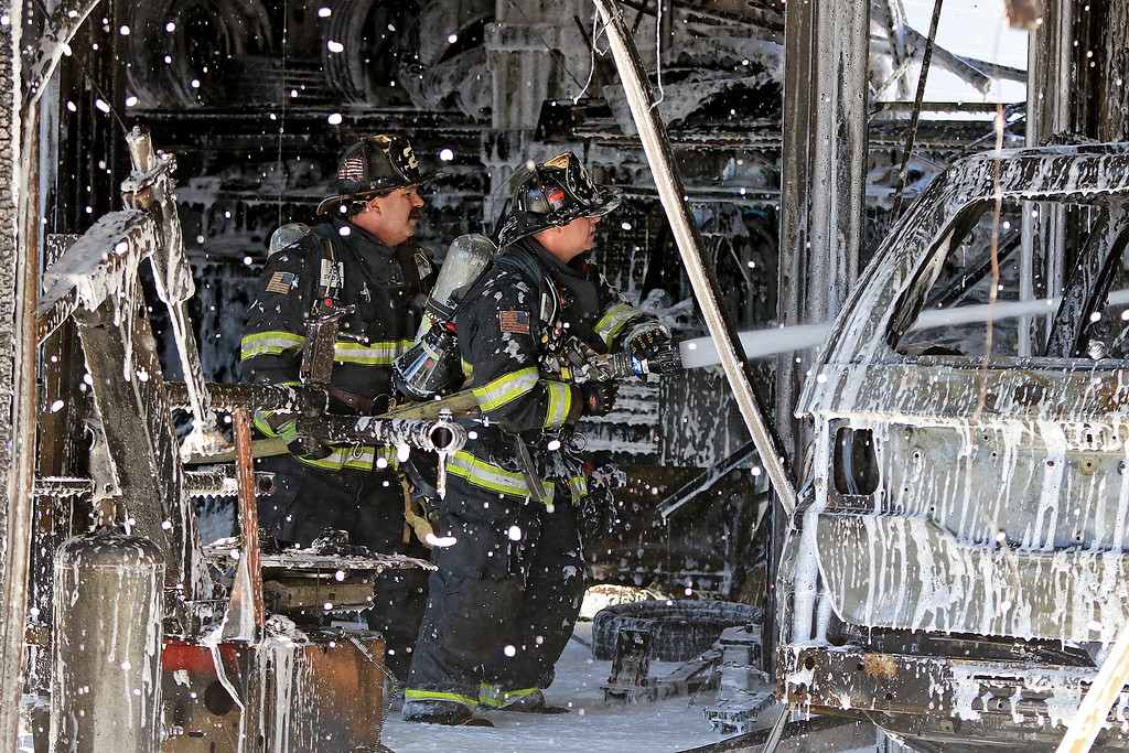 . A fire broke out at the Sunoco station on Route 13 in Leominster early on Thursday morning. Firefighters spray some foam on a now destroy car that was in one of the bays as the fire broke out. SENTINEL & ENTERPRISE/JOHN LOVE