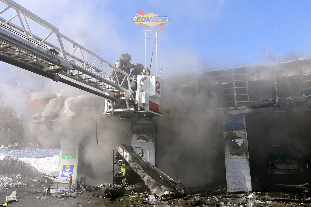 . A fire broke out at the Sunoco station on Route 13 in Leominster early on Thursday morning. Firefighters work from the bucket on the ladder truck as they fight the fire. SENTINEL & ENTERPRISE/JOHN LOVE
