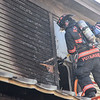 KRISTOPHER RADDER — BRATTLEBORO REFORMER<br /> A Bellows Falls firefighter rips away some siding to attack a hotspot that was smoking.