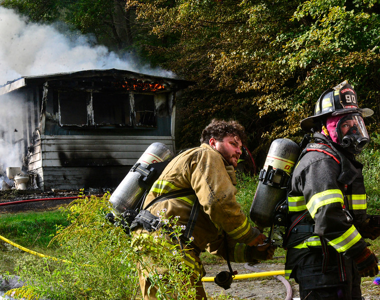 KRISTOPHER RADDER — BRATTLEBORO REFORMER<br /> A firefighter helps another put an air tank on during a two-alarm fire at 1390 Coolidge Highway, in Guilford, Vt., early Monday, Sept. 14, 2020. The home was engulfed in flames when the first crew arrived on the scene.
