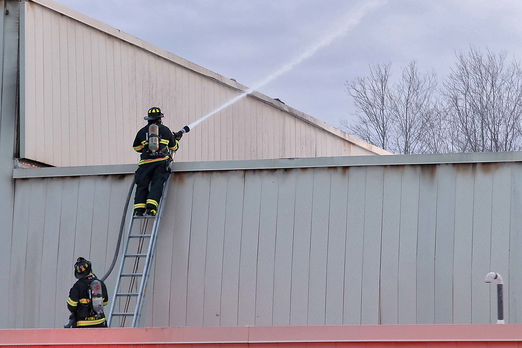 . Fire Departments from towns all around Ayer were on scene at Advanced Vacuum Systems\' a Speciality Furnace Equipment business in Ayer on Friday night to help out at a incident that had one person lifefighted. A firefigher shoots water on the roof of the building on Fitchburg Road.  SENTINEL & ENTERPRISE/JOHN LOVE