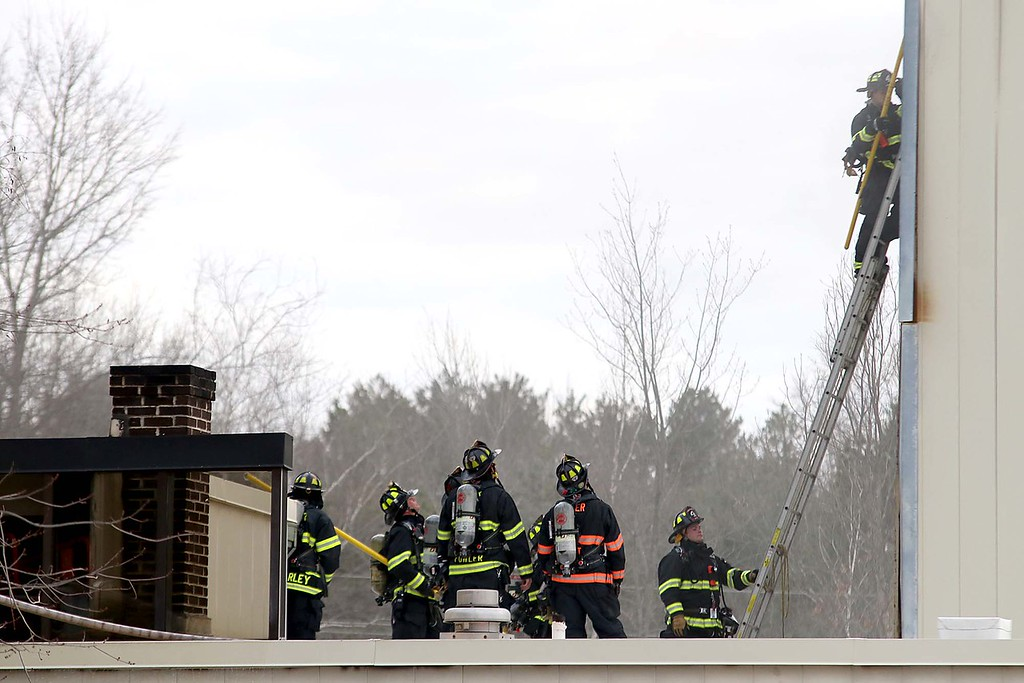 . Fire Departments from Towns all around Ayer were on scene at Advanced Vacuum Systems\' a Speciality Furnace Equipment business in  Ayer on Friday night to help out at a incident that had one person lifefighted. Firefighters work on the roof of the building on Fitchburg Road. SENTINEL & ENTERPRISE/JOHN LOVE