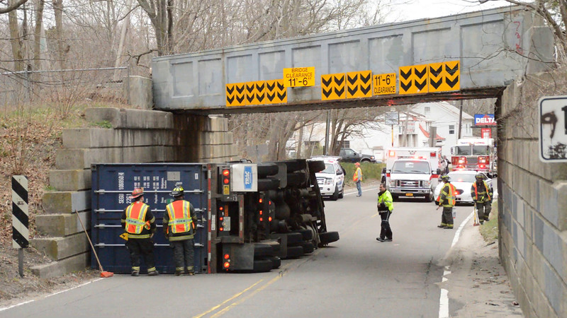 Overturned tractor trailer in Center Moriches, Friday, April 18, 2014. The Center Moriches F.D. and officers from the SCPD 7th Pct. responded at approx. 7:10 a.m. to this overturned tractor trailer on Montauk Hgwy. between Wilcox Ave. and Old Neck Rd. The driver, who received only minor injuries, while traveling east bound on Montauk Hgwy., apparently struck the LIRR overpass causing his truck to flip onto it's side. It is unknown what his cargo was at this time. Montauk Hgwy. was closed in both directions and the LIRR will be delayed for some time until the vehicle is removed.