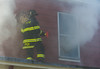 A Fitchburg firefighter prepares to vent a 2nd floor window on Cottage St. SENTINEL&ENTERRPRISE/ Jim Marabello