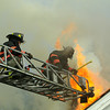 Heavy fire vents the roof after the opening up<br /> <br /> Photo Scott LaPrade