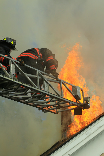 Firefighters prepare to exit the roof via the aerial after opening up the roof.<br /> <br /> Photo Scott LaPrade