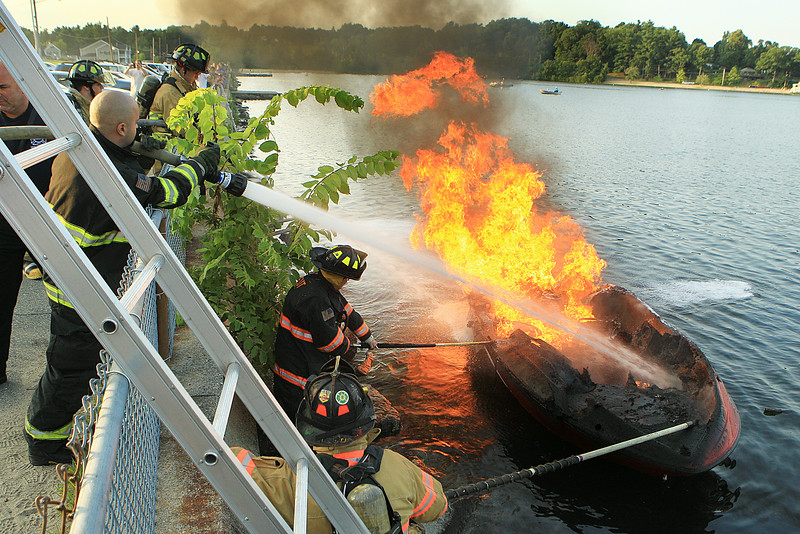 Leominster Firefighter Andrew Dunner sprays water down on the boat as father Lt.Gary Dunner holds on to the boat with a hook preventing it from moving away.<br /> <br /> Photo Scott LaPrade