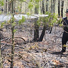 Firefighters fight a brush fire off of Wachusett Street in Leominster  on Monday around noon. Spraying down the hot embers is Leominster firefighter Shawn Phillips. SENTINEL & ENTERPRISE/JOHN LOVE