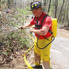 Firefighters fought a brush fire off of Wachusett Street in Leominster  on Monday around noon. Leominster firefirghter Rick Cormier uses a hand held water sprayer to help put out the fire. SENTINEL & ENTERPRISE/JOHN LOVE