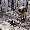 Firefighters fight a brush fire off of Wachusett Street in Leominster  on Monday around noon. using his ax to help keep down the fire is fSterling firefighter James Divirgilo. SENTINEL & ENTERPRISE/JOHN LOVE