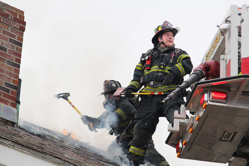 A fire broke out at 71-73 Boutelle Street on Monday afternoon. Firefighters work on breaking through the roof to get at the fire. SENTINEL & ENTERPRISE/JOHN LOVE
