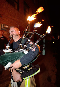 """FF Kenny Rybka of the Cleveland OH FD """"fires up"""" his pipes prior to marching through the streets of Colorado Springs the night before the 2013 IAFF Fallen FF Memorial"""