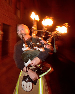 "FF Kenny Rybka of the Cleveland OH FD ""fires up"" his pipes prior to marching through the streets of Colorado Springs the night before the 2013 IAFF Fallen FF Memorial"