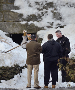 A Mass State Police detective enters  a tunnel beneath a retaining wall behind 276 Kimball St, Fitchburg in the search for the missing 5 year old from that address, while a State Police K9 trooper confers with Fitchburg PD detectives around 8 a.m. on Dec 21st, 2013