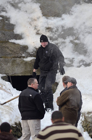 A Mass State Police K9 officer emerges from a tunnel beneath a retaining wall behind 276 Kimball St, Fitchburg in the search for the missing 5 year old from that address