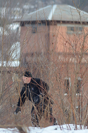 A Mass State Police K9 officer emerges from the brush at the top of an embankment across from 276 Kimball St, Fitchburg in the search for the missing 5 year old from that address