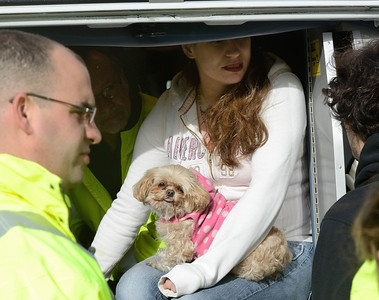 A resident of an apartment building on Westminster St holds one dog and comforts another in the back of a MedStar ambulance after they were rescued by Fitchburg FFs at a 2nd Alm fire. Over 25 people were displaced.
