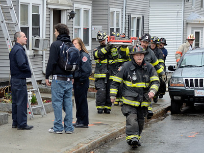 Leominster  FF Mark Matley leads the way as Leominster FFs remove a 35' ground ladder from the rear of the building at a 2nd Alm fire on Westminster St in Fitchburg. Over 25 people were displaced. Two dogs were rescued from an apartment. At left, Fire Prevention officers talk with a tenant of the building.