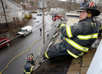 Fitchburg FF John Girouard assisted by FF Sean Roy, prepares to get off a wet slate roof at a 2nd Alm fire on Westminster St Over 25 people were displaced. Two dogs were rescued from an apartment.