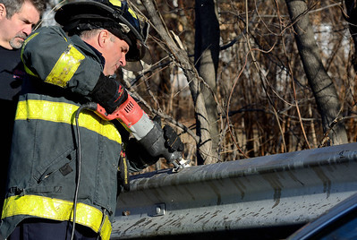 Fitchburg FF Jim Nault works to remove a guardrail embedded into a car that crashed into it on Pratt Rd.