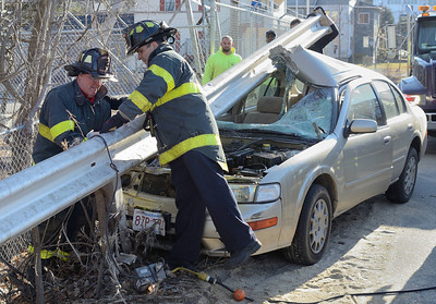 Fitchburg FFs Tom O'Kane (l) and Jim Nault ® work to remove a guardrail from a vehicle that struck it on Pratt Rd across from Parkhill Park. The driver suffered minor injuries.