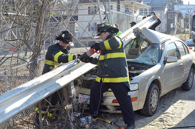 Fitchburg FFs Tim O'Kane (l) and Jim Nault ® work with to remove a section of guardrail struck by a motor vehicle on Pratt Rd across from Parkhill Park. The driver suffered minor injuries.