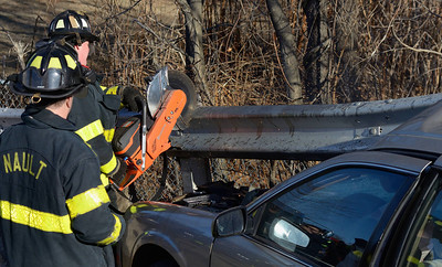 Fitchburg FF Tim O'Kane uses a power saw to remove a guardrail embedded into a car that crashed into it on Pratt Rd. Also in photo is FF Jim Nault. The driver suffered minor injuries.