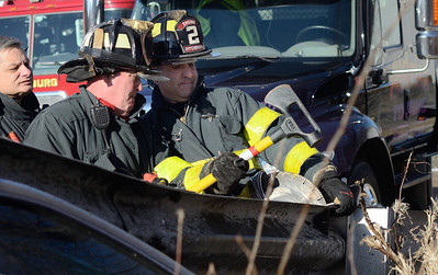 Fitchburg FFs Tim O'Kane (l) and Jim Nault ® work to remove a guardrail embedded into a car that crashed into it on Pratt Rd. In the background is Lt Dave Gravel. The driver of the car suffered minor injuries.