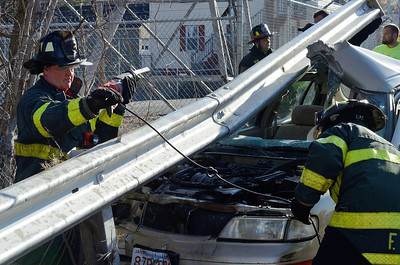 Fitchburg FFs Tim O'Kane (l) and Jim Nault ® work to remove a guardrail embedded into a car that crashed into it on Pratt Rd.