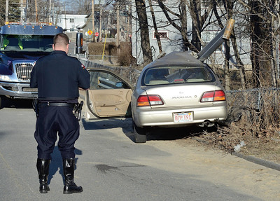 A Fitchburg police officer investigates a car that crashed through a guardrail on Pratt Rd across from Parkhill Park. The driver suffered minor imjuries.