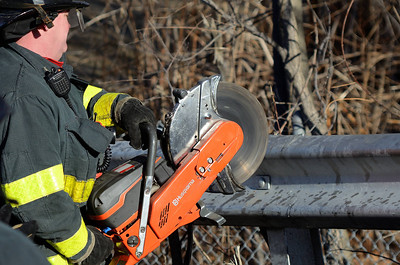 Fitchburg FF Tim O'Kane uses a power saw to remove a guardrail embedded into a car that crashed into it on Pratt Rd.