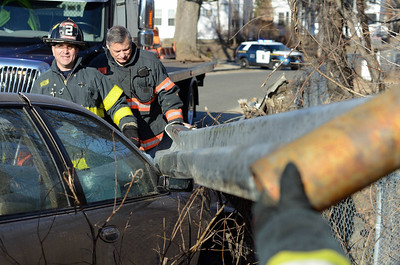 Fitchburg FF Jim Nault (l) and Lt Dave Gravel ® work at removing a guardrail struck by a vehicle on Pratt Rd across from Parkhill Park. The driver suffered moinor injuries.