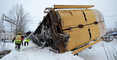 A Gardner Fire Lt. walks past a car carrier lying on it's side at the South Main St crossing in Gardner, Mass.