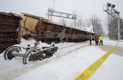 A loaded, derailed car carrier lies on it's side at the South Main St crossing in Gardner, Mass.