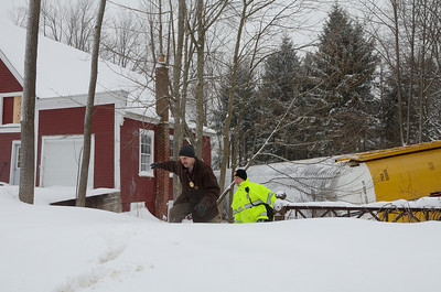 Gardner police walk through the snow away from one of 4 derailed car carriers lying on it's side up against a South Main St residence in Gardner, Mass.
