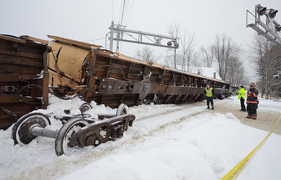 A derailed, loaded car carrier lies on it's side at the South Main St crossing in Gardner, Mass.