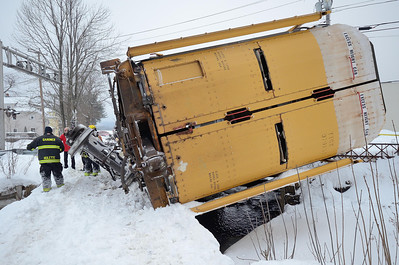 A car carrier lies on it's side at the South Main St crossing in Gardner, Mass.