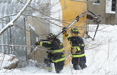 Gardner firefighters trudge through knee deep snow alongside one of 4 car carriers lying on it's side at the South Main St crossing in Gardner, Mass.
