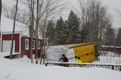 One of 4 derailed car carriers lies on it's side up against a South Main St residence in Gardner, Mass.